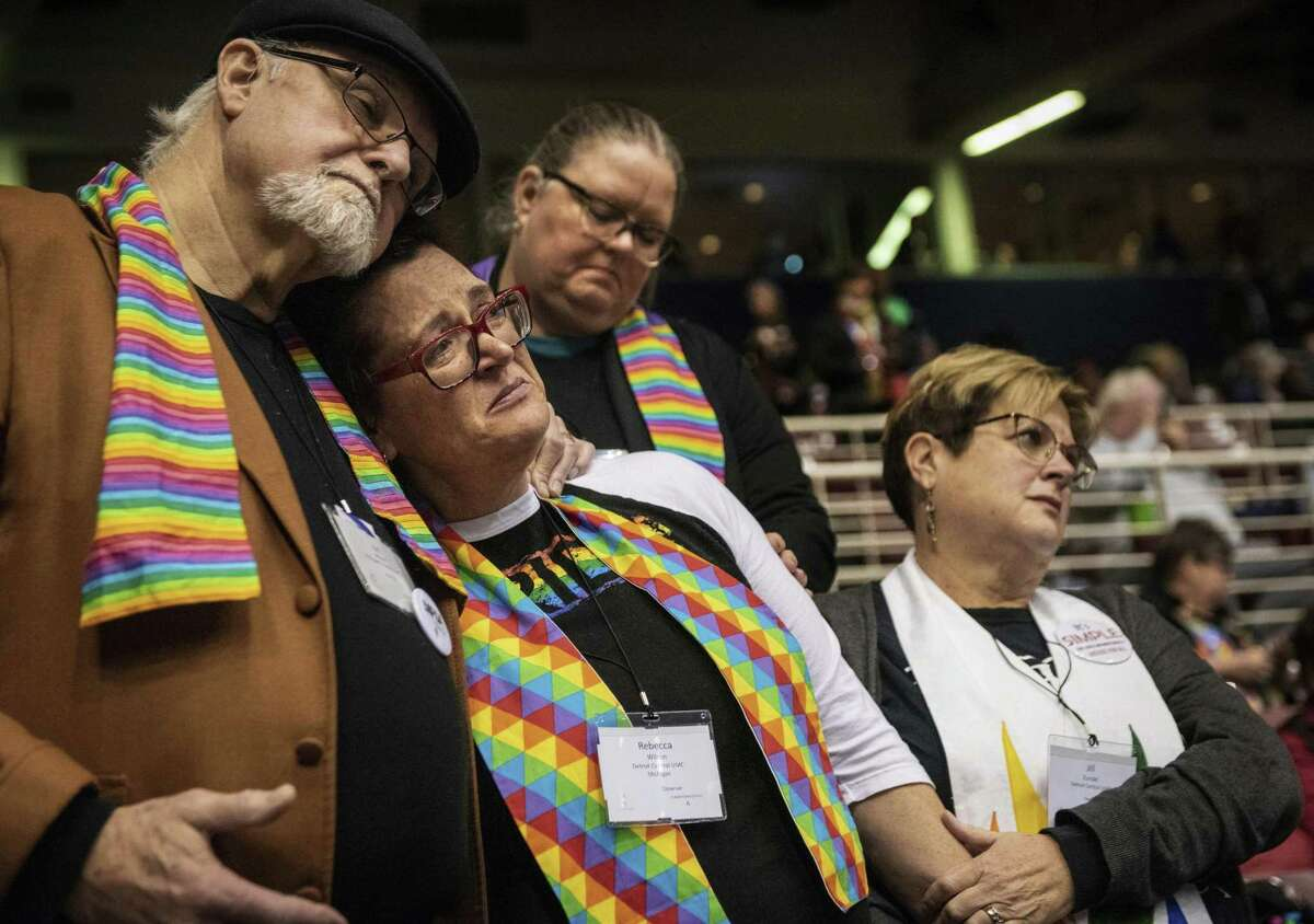 FILE - In this Feb. 26, 2019, file photo, Ed Rowe, left, Rebecca Wilson, Robin Hager and Jill Zundel, react to the defeat of a proposal that would allow LGBT clergy and same-sex marriage within the United Methodist Church at the denomination's 2019 Special Session of the General Conference in St. Louis, Mo. The church ended a pivotal conference on Feb. 26 in a seemingly irreconcilable split over same-sex marriage and the ordination of LGBT clergy. (AP Photo/Sid Hastings, File)