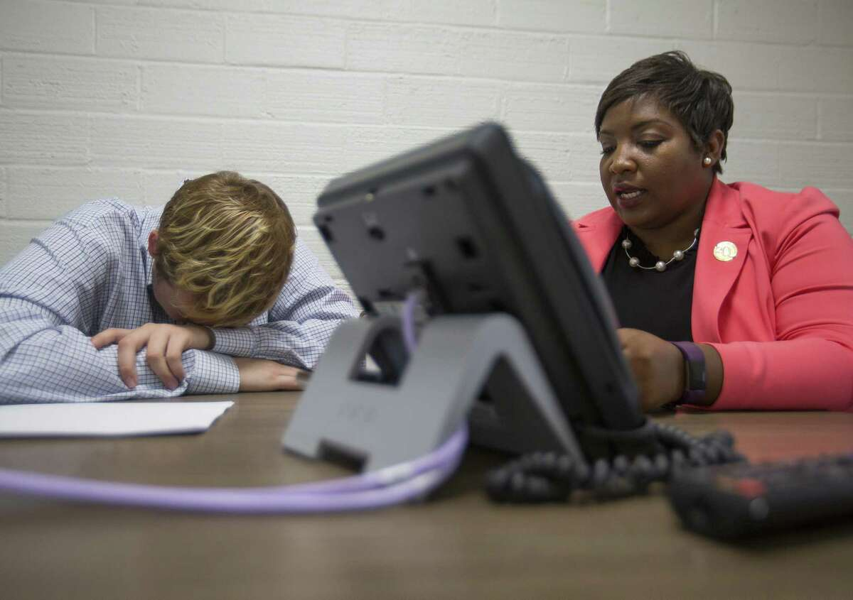 A tired Alec Chester, 20, puts his head down on his arms as he reviews a housing voucher application with housing program coordinator Joanquinta White at the HAY Center in Houston, Thursday, March 7, 2019. A federal grant recently provided $700,000 for housing vouchers in the Houston area for young adults aging out of foster care.