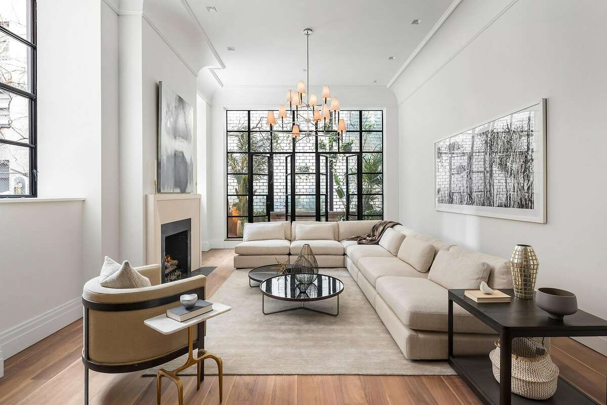 A neutral color palette and monochromatic artwork lend contrast to a metallic chandelier within this residence in New York's West Village that was staged by San Francisco-based studio D.