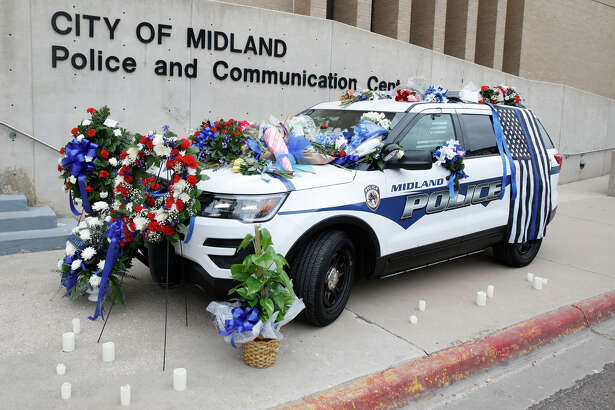 Flowers adorn the patrol vehicle belonging to Midland Police Department Officer Nathan Heidelberg, parked outside the police station, March 7, 2019. A statement released by the city indicated the vehicle would be parked outside the station in memory of the officer who was shot by a homeowner while responding to a burglary alarm on March 5, 2019. James Durbin / Reporter-Telegram