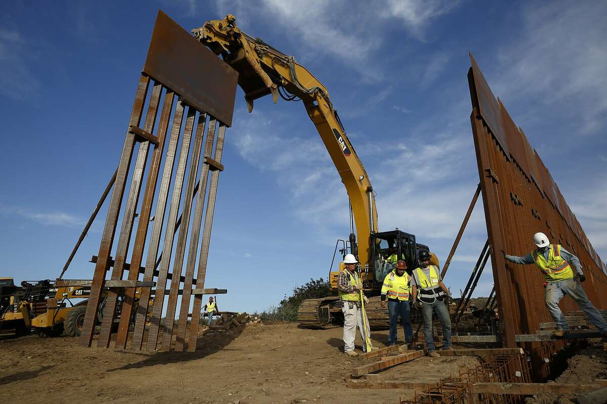 FILE - In this Jan. 9, 2019 file photo, construction crews install new border wall sections seen from Tijuana, Mexico. Sen. Dick Durbin, D-Ill., says the Pentagon is planning to tap $1 billion in leftover funds from military pay and pensions accounts to help President Donald Trump pay for his long-sought border wall. Durbin told The Associated Press,