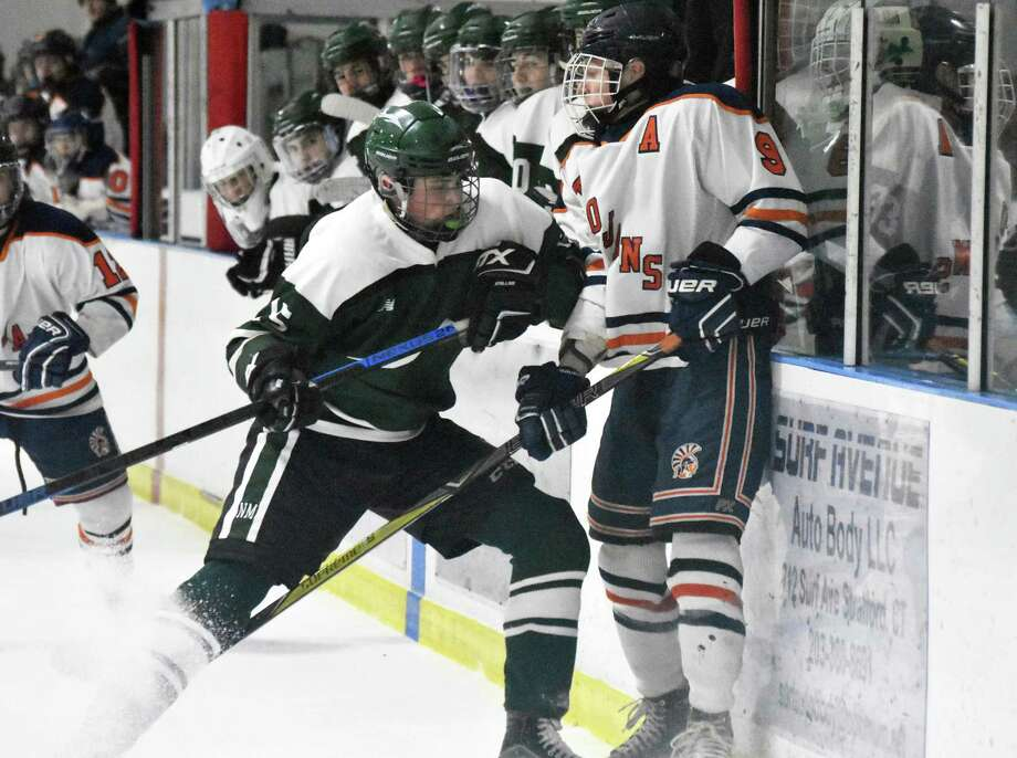 New Milford's Matthew Hassiak hits Lyman Hall co-op's Connor Statton in the quarterfinals of the Division III tournament at Wonderland Ice Arena, Bridgeport on Thursday, March 7, 2019. (Pete Paguaga, Hearst Connecticut Media) Photo: Pete Paguaga / Hearst Connecticut Media / Connecticut Post