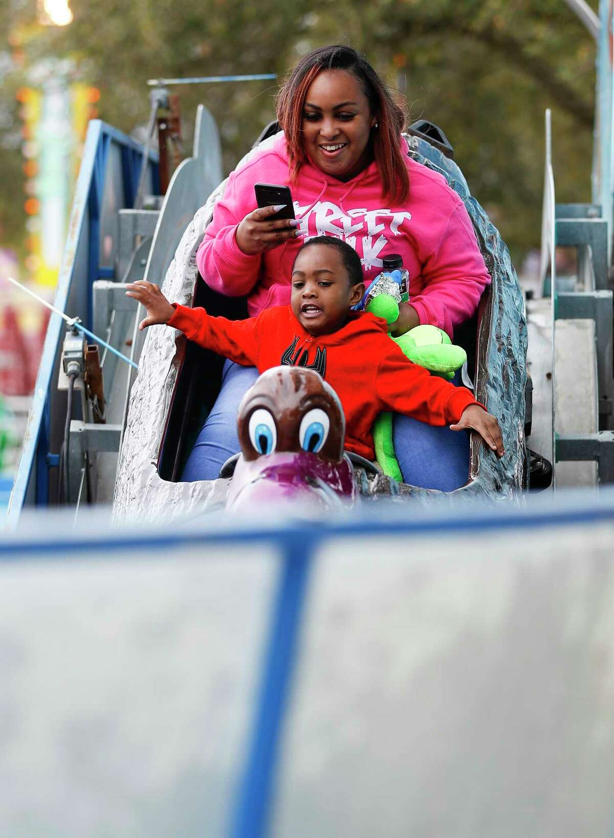 Kristian Barker takes photos of Majik Bishop, 3, as they rode the Pelican Spash in the kid's carnival area at the Houston Livestock Show and Rodeo at NRG Center, Thursday, March 7, 2019, in Houston.