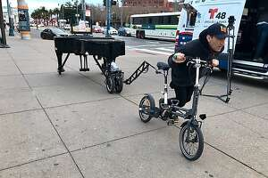 Davide Martello pushes his bicycle, which is towing a grand piano, along the Embarcadero in San Francisco on March 7, 2019.