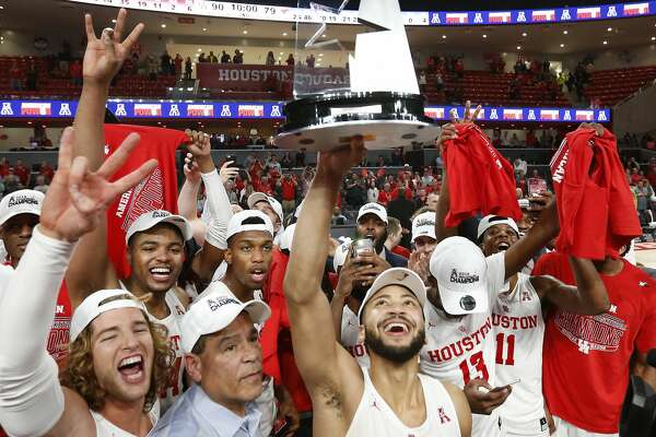 Houston guard Galen Robinson Jr. (25) holds up the American Athletic Conference championship trophy as the Cougars celebrate after beating Southern Methodist 90-79 to win at least a share of the AAC at Fertitta Center on Thursday, March 7, 2019, in Houston.