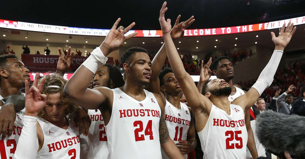 Houston guard Landon Goesling (2), forward Breaon Brady (24) and guard Galen Robinson Jr. (25) celebrate after beating Southern Methodist 90-79 to win at least a share of the American Athletic Conference title at Fertitta Center on Thursday, March 7, 2019, in Houston.