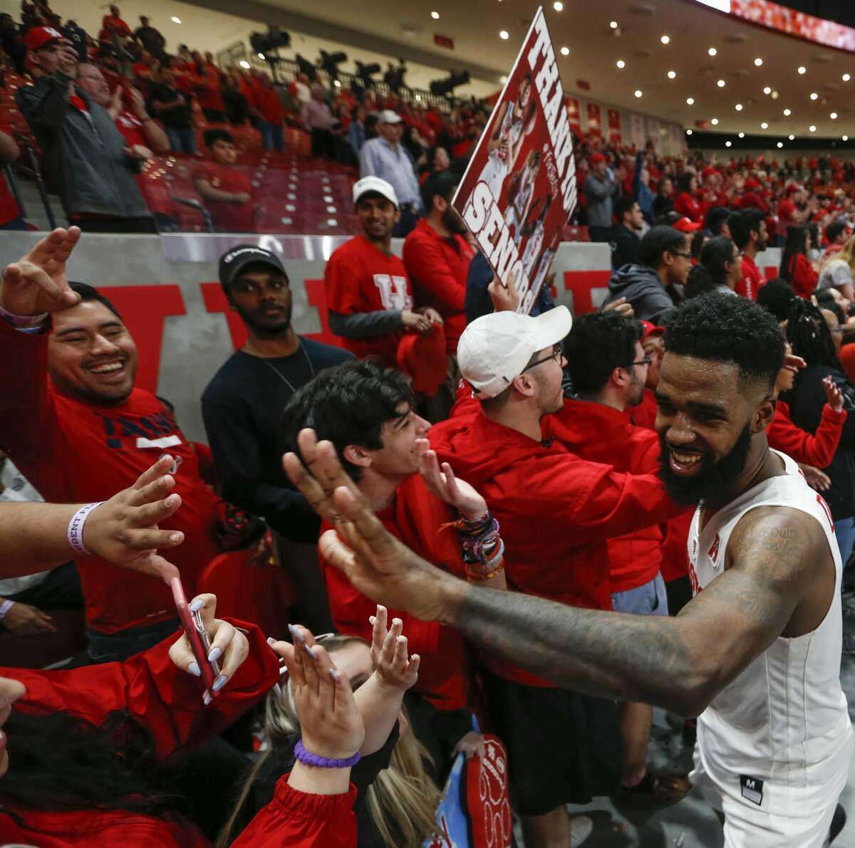 Houston guard Corey Davis Jr. (5) high fives fans as the Cougars celebrate after beating Southern Methodist 90-79 to with the AAC at Fertitta Center on Thursday, March 7, 2019, in Houston.