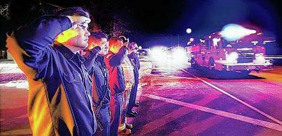 "East Alton firefighters line up and salute as a long procession of firetrucks and police cars pass their station escorting the body of Godfrey Fire Capt. Jacob ""Jake"" Ringering, 37, from Alton Memorial Hospital to the Madison County Morgue in Edwardsville. Ringering died from injuries suffered while battling a fire in the 4000 block of Culp Lane. Photo: John Badman 
