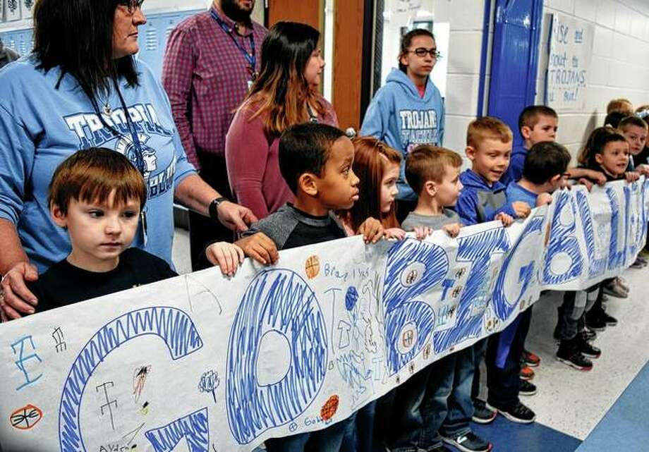 Students from Triopia Elementary School hold a sign Thursday as the boys basketball team prepares to leave for the Illinois High School Association Class 1A final four competition in Peoria. Photo: Samantha McDaniel-Ogletree | Journal-Courier