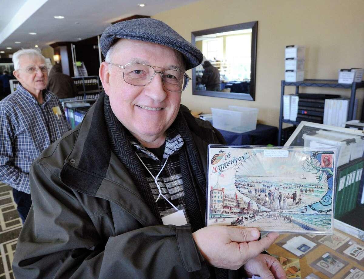 A postcard vendor holds up a mailed 1901 postcard sent July 3rd from Narragansett, Rhode Island, at a past Ephemera Fair at the Hyatt Regency Greenwich, in 2017.