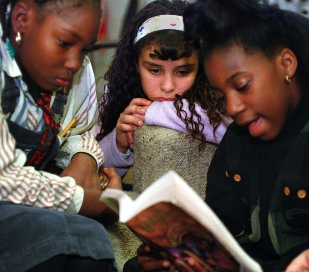 Melissa Harris, 9, reads from a Harry Potter book while Chelcy Moore, 9, left, and Isaura Torres, 10, listen during a Harry Potter discussion group at the Albany Girls Club on Monday November 15, 1999. (Times Union Staff Photo by Philip Kamrass)