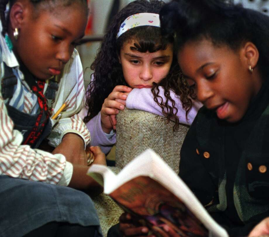 Melissa Harris, 9, reads from a Harry Potter book while Chelcy Moore, 9, left, and Isaura Torres, 10, listen during a Harry Potter discussion group at the Albany Girls Club on Monday November 15, 1999. (Times Union Staff Photo by Philip Kamrass) Photo: PHILIP KAMRASS, DG / ALBANY TIMES UNION