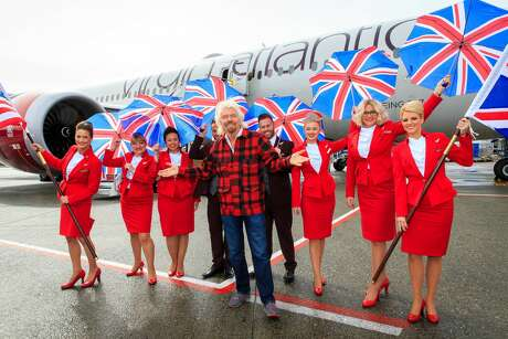 Sir Richard Branson and flight crew touch down at Seattle Tacoma International Airport. This week Virgin Atlantic removed a makeup requirements for female flight attendants