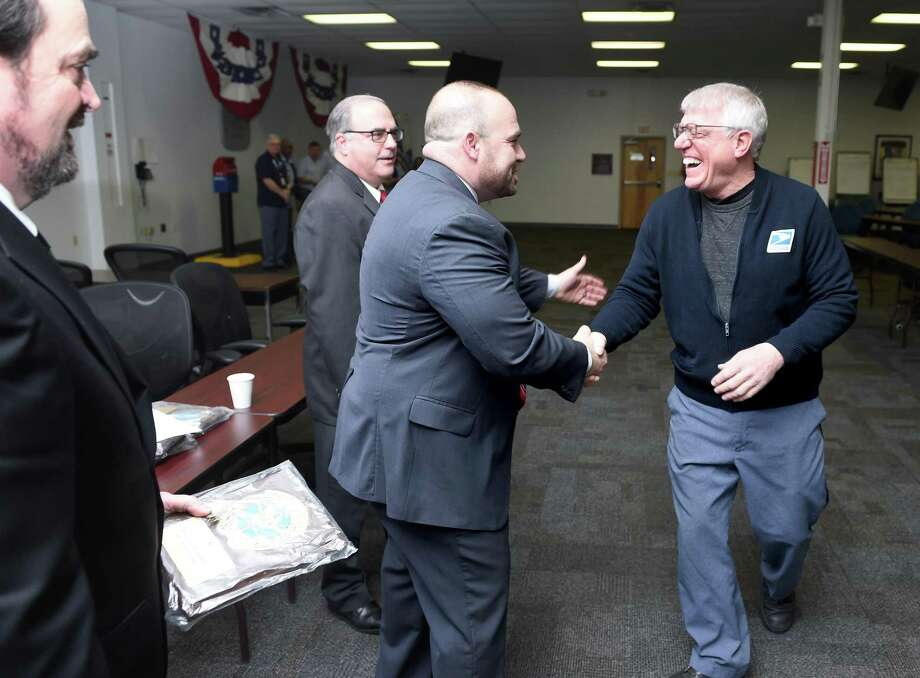 New Haven Postmaster Thomas Sullivan (center) congratulates letter carrier Vincent Corniello (right) who was among 40 recipients of the National Safety Council's Million Mile Award at the Brewery Street Post Office in New Haven on March 8, 2019. Recipients of the award have driven for over 30 years without any non preventable at-fault accidents. Carriers out of the Brewery Street Post Office drive over 58,000 miles per month. From left are John O'Mara, manager of customer service, David Mastroianni, Connecticut Valley District Manager, Sullivan and Corniello. Photo: Arnold Gold / Hearst Connecticut Media / New Haven Register