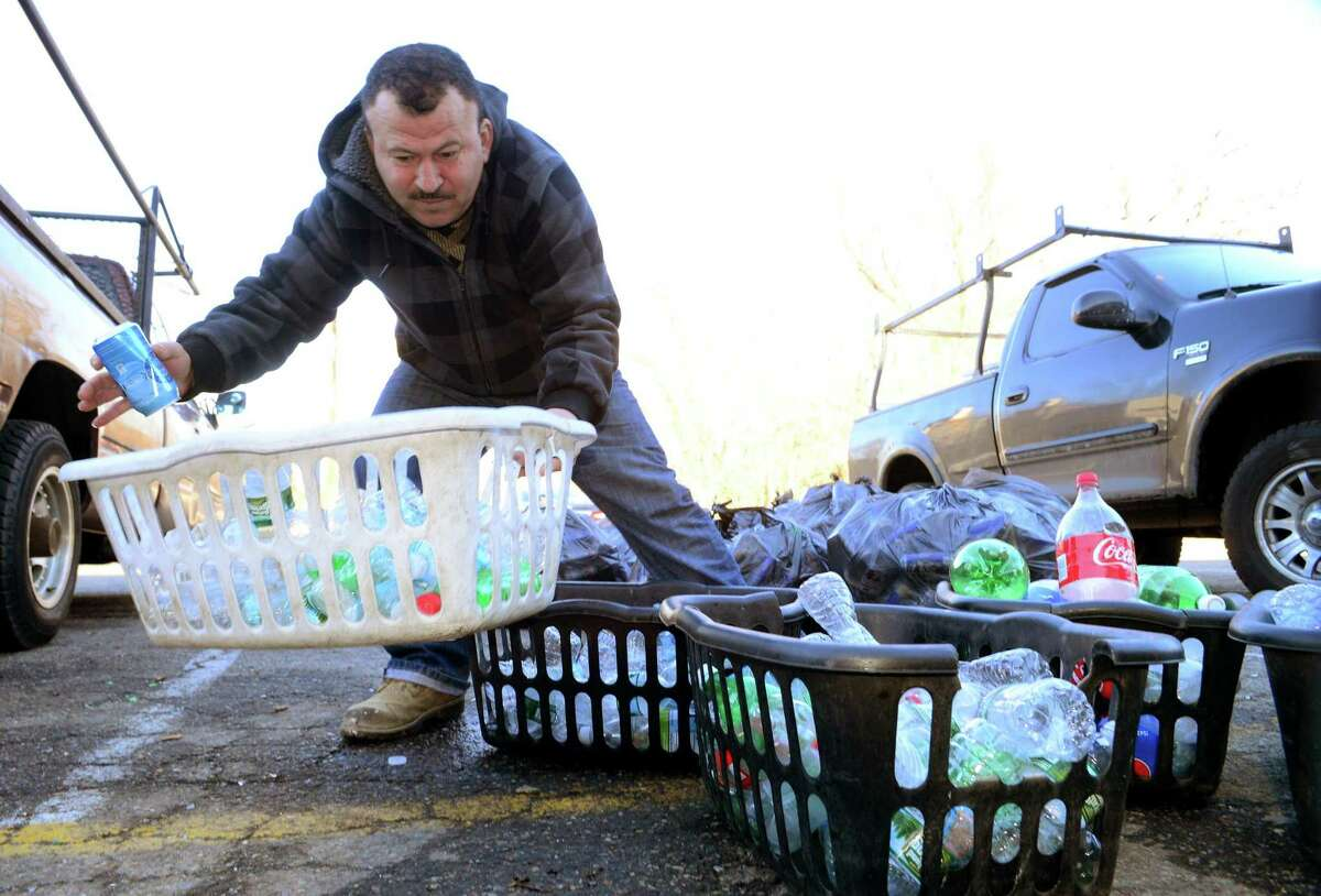 A Bridgeport resident organized bottles in front of MLI Redemption Services in Stratford, in a 2017 file photo.