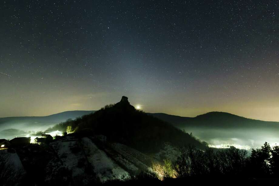 The white glow of zodiacal light is visible in the night sky as photographed near Hajnacka, southern Slovakia Feb. 7. The faint light is caused by interplanetary dust reflecting sunlight. The astronomical phenomenon in the temperate zones is most clearly visible in February and March after sunset and in September and October before sunrise, when the zodiac is positioned at a steep angle to the horizon. Photo: Peter Komka / Associated Press / MTVA - Media Service Support and Asset Management Fund