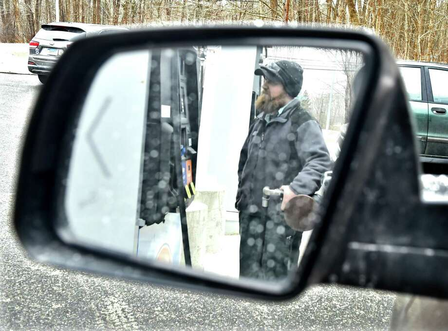 Guilford Connecticut - Wednesday February 18, 2019: Brad Lindberg, a car mechanic at the Four Corners Gas Station in Guilford puts gas into a customers automobile. The Four Corners Gas Station on Route 80 in Guilford is an old fashioned full service gas station Photo: Peter Hvizdak / Hearst Connecticut Media / New Haven Register