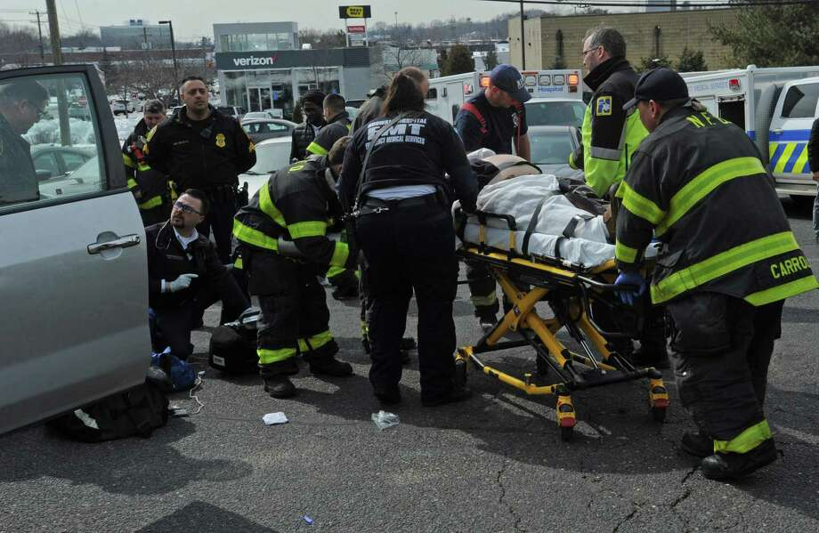 Emergency personel respond to 280 Connecticut Ave. where a driver fell under his vehicle as it rolled backward at the parking lot of Crossroad Card and Gift Friday, March 7, 2018, in Norwalk, Conn. Photo: Erik Trautmann / Hearst Connecticut Media / Connecticut Post