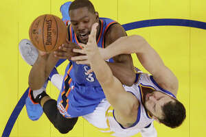 Oklahoma City Thunder's Kevin Durant, top, goes up for a shot as Golden State Warriors' Andrew Bogut defends during the first half in Game 1 of the NBA basketball Western Conference finals Monday, May 16, 2016, in Oakland, Calif. Oklahoma City won 108-102.