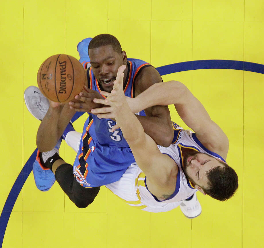 Oklahoma City Thunder's Kevin Durant, top, goes up for a shot as Golden State Warriors' Andrew Bogut defends during the first half in Game 1 of the NBA basketball Western Conference finals Monday, May 16, 2016, in Oakland, Calif. Oklahoma City won 108-102. Photo: AP Photo/Marcio Jose Sanchez