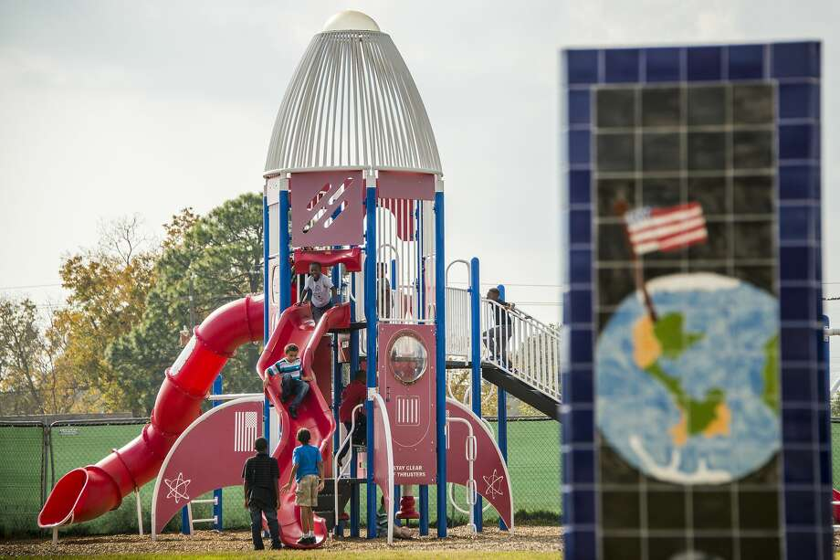 Behind one of seven obelisks displaying student art work depicting a space theme, students at McWhirter Elementary play on rocket-shaped playground equipment on Monday, Dec. 15, 2014, in Webster. Photo: File