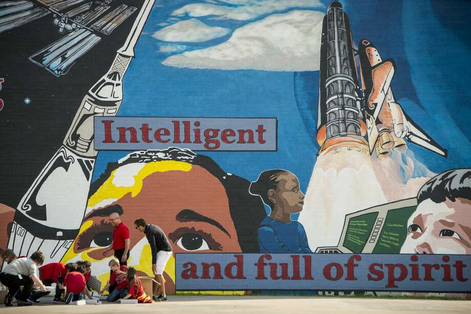In front of a mural on the school gym depicting students gazing toward space, members of the robotics team at McWhirter Elementary work on a project on Dec. 15, 2014, in Webster. Photo: File