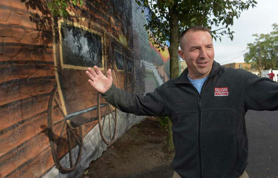 Jason Milligan, owner of Milligan Realty, stands next to the mural he had painted on his building at 97 Wall Street Friday, October 19, 2018, in Norwalk, Conn. Milligan, who remains the subject of a lawsuit after purchasing those and other properties within the stalled Wall Street Place development area. Photo: Erik Trautmann / Hearst Connecticut Media / Norwalk Hour