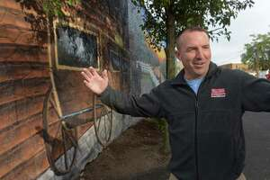Jason Milligan, owner of Milligan Realty, stands next to the mural he had painted on his building at 97 Wall Street Friday, October 19, 2018, in Norwalk, Conn. Milligan, who remains the subject of a lawsuit after purchasing those and other properties within the stalled Wall Street Place development area.