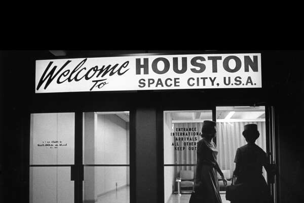 "12/1967 - Flight attendants enter the international arrivals entrance at Hobby Airport. Arrivals are greeted with a ""Welcome to HOUSTON SPACE CITY, U.S.A."" sign over the door."