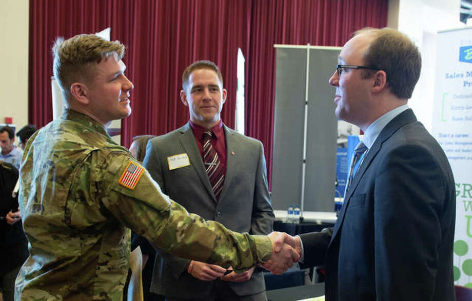 L-R: Jared Wilson, a senior majoring in business management, shakes hands with Steve McGuire of Buckeye International as Matt Reinholz looks on. Photo: For The Intelligencer