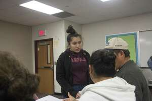 """Zared Romero, 17, helps her parents learn the verb """"to be"""" at an ESL class at Magnolia West High School on Feb. 19. Magnolia West High School hosts an adult ESL class every Tuesday and Thursday evening."""
