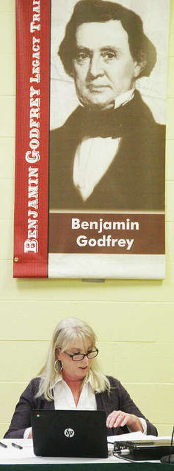 New Godfrey Village Clerk Bethany Bohn sits under a banner for town namesake Benjamin Godfrey after been sworn in at Tuesday's Village Board meeting. She replaces long-time clerk Pam Whisler, who retired in December and had been the only person to hold the position until Tuesday. Photo: Scott Cousins | The Telegraph
