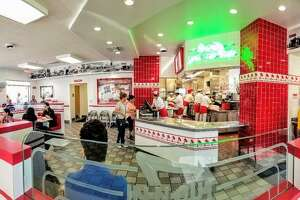 In-N-Out has been subtly making changes to its decor and has updated a handful of In-N-Out locations, including this restaurant in Santa Ana, Calif. Among the updates are the neon green sign above the register, the addition of vintage photos of the original In-N-Outs, and upgraded wallpaper and light fixtures.