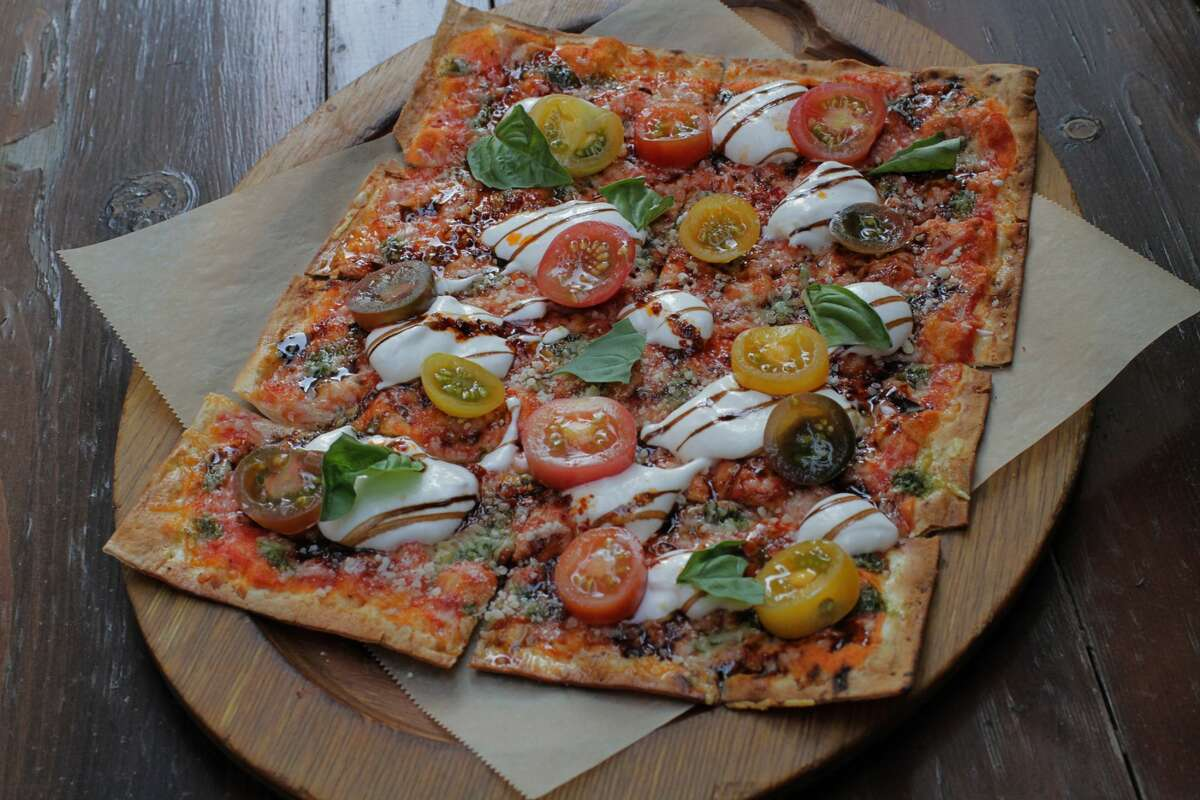 The burrata and heirloom tomato crisp features pomodoro sauce, pesto, mozzarella burrata cheese, Parmesan, and balsamic reduction.
