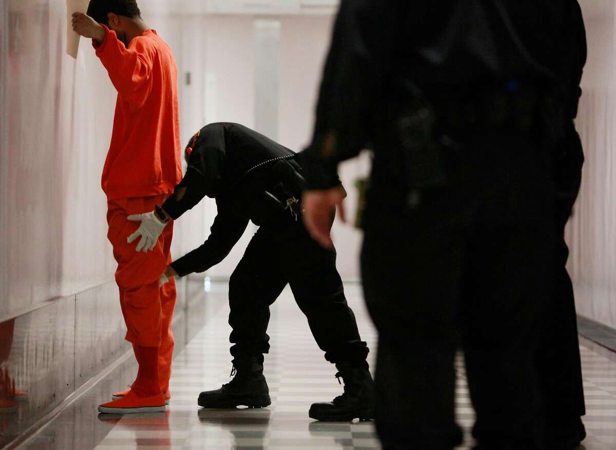 An inmate is patted down before entering the Five Keys Charter School in San Francisco County Jail #5 - San Bruno Complex on Monday, January 28, 2013 in San Bruno, Calif.