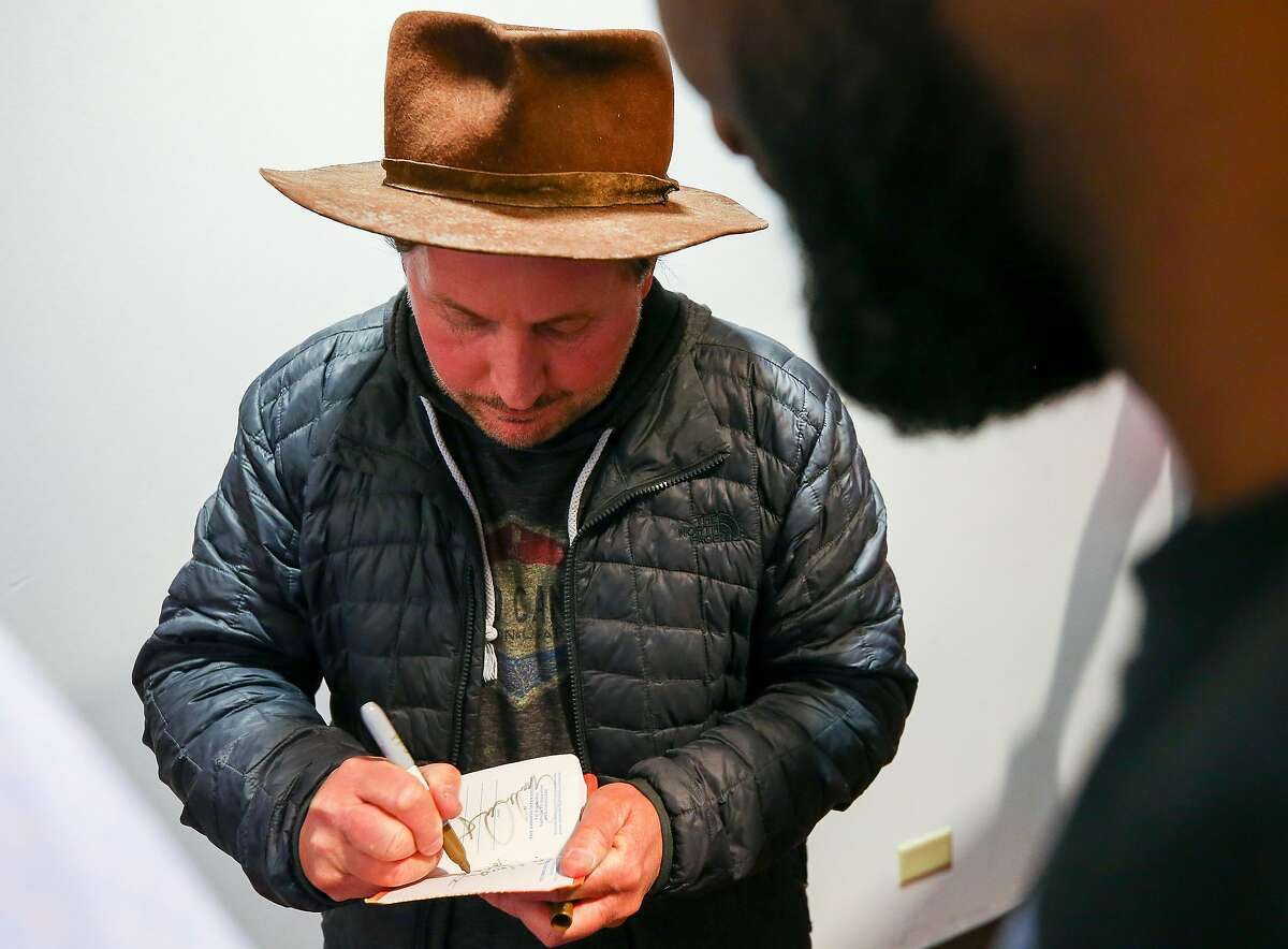 Emilio Estevez, center, signs an autograph for Jermaine Wright after an advanced screening of