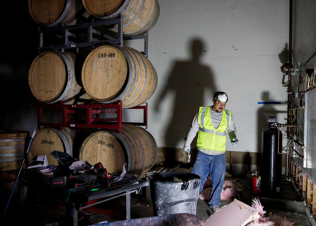 Crews work to remove drywall and continue to clean up damage caused by floodwaters inside Pax Wines at The Barlow shopping plaza in Sebastopol, Calif. Friday, March 8, 2019.