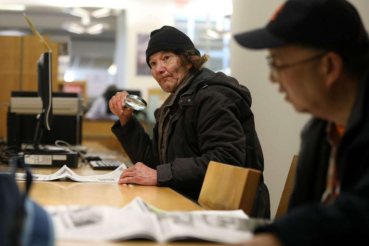 Paul Michael Landon, who says he has been dealing with homelessness for about a year, reads a newspaper at the San Francisco Main Library on Thursday, March 7, 2019 in San Francisco, Calif. Landon says he goes to the library almost daily and likes to study music and read newspapers at the library.