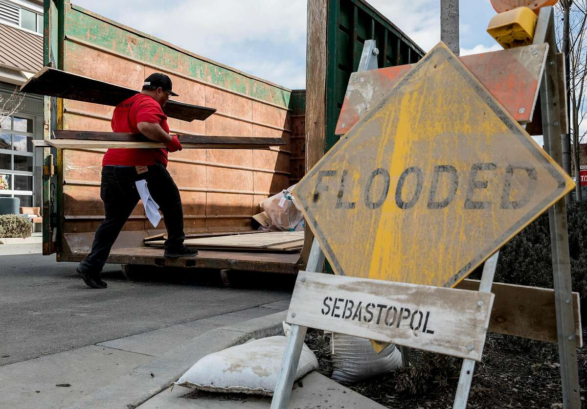 Crews continue to clean up damage caused by floodwaters at The Barlow shopping plaza in Sebastopol, Calif. Friday, March 8, 2019.
