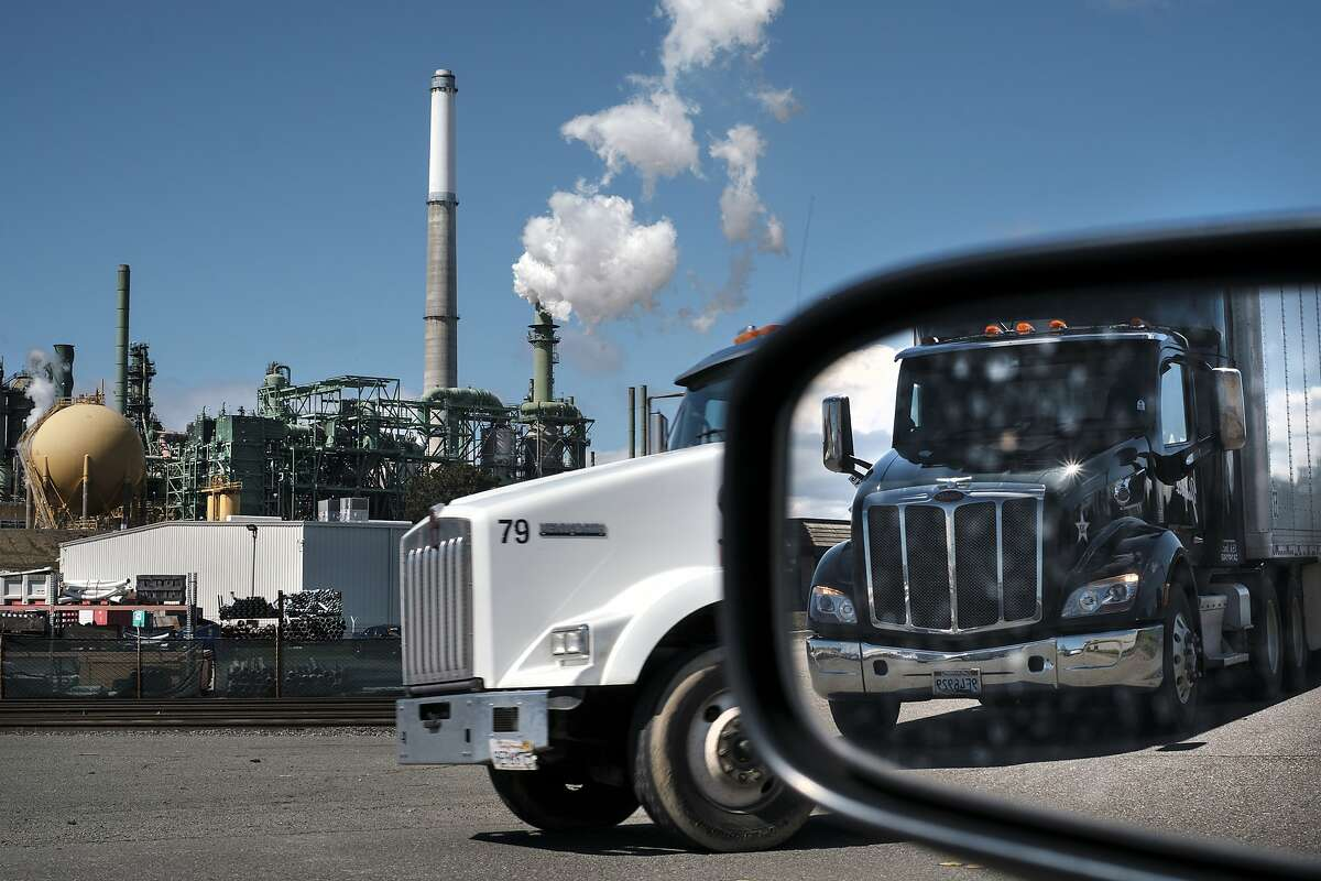 A truck is reflected in a side mirror as it passes in front of the Valero Benicia Refinery in Benicia, Calif., on Friday, March 8, 2019. Assembly woman Nancy Skinner is proposing bill that would effectively ban diesel trucks by 2030