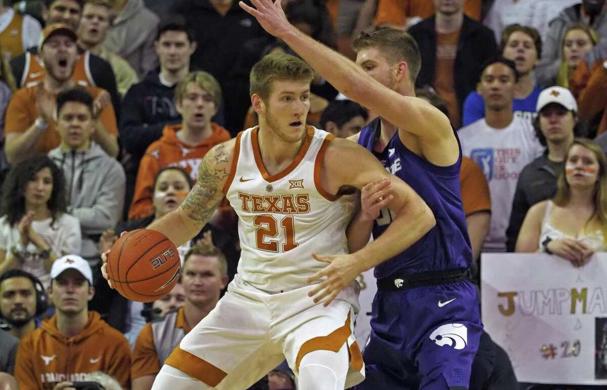 Texas' Dylan Osetkowski (21) looks to drive against Kansas State's Dean Wade during the first half Feb. 12 in Austin.