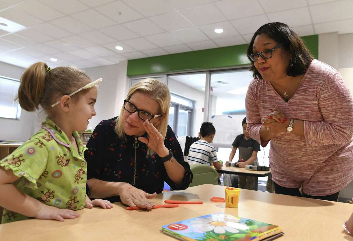 Pamela Davis, second from left, a kindergarten teacher at Menchaca Early Childhood Center in the Southside ISD, chats with student Carly Schnautz as Jennifer Trevino, right, Davis' former classmate at Business Careers High School, listens. Davis recently donated a kidney to Trevino, who credits Davis with saving her life. But Davis said that, on the contrary, Trevino saved her life because she had to lose 150 pounds to donate.
