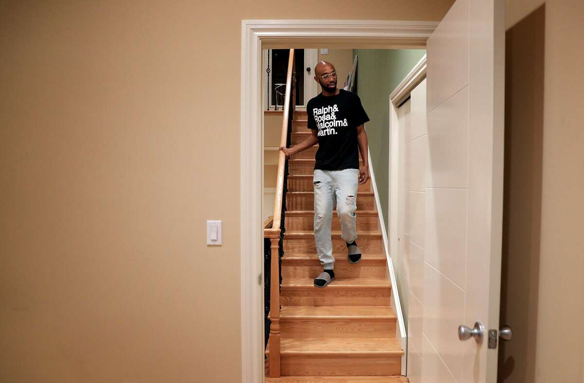 Randy Jordan walks down stairs near housemates' rooms in their Bungalow, co-living home in Oakland, Calif., on Monday, February 4, 2019. Bungalow is a co-living startup that leases big houses and then rents individual rooms that share a common spaces like kitchen, living room, and bathrooms.