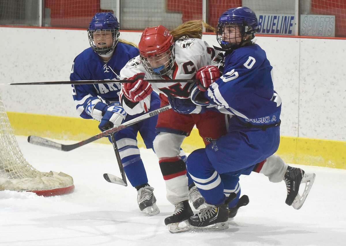 New Canaan's Jess Eccleston (7) and Darien's Nelle Kniffin (20) and Evelyn Hidy (8) mix it up during a game at the Darien Ice House on Jan. 26.