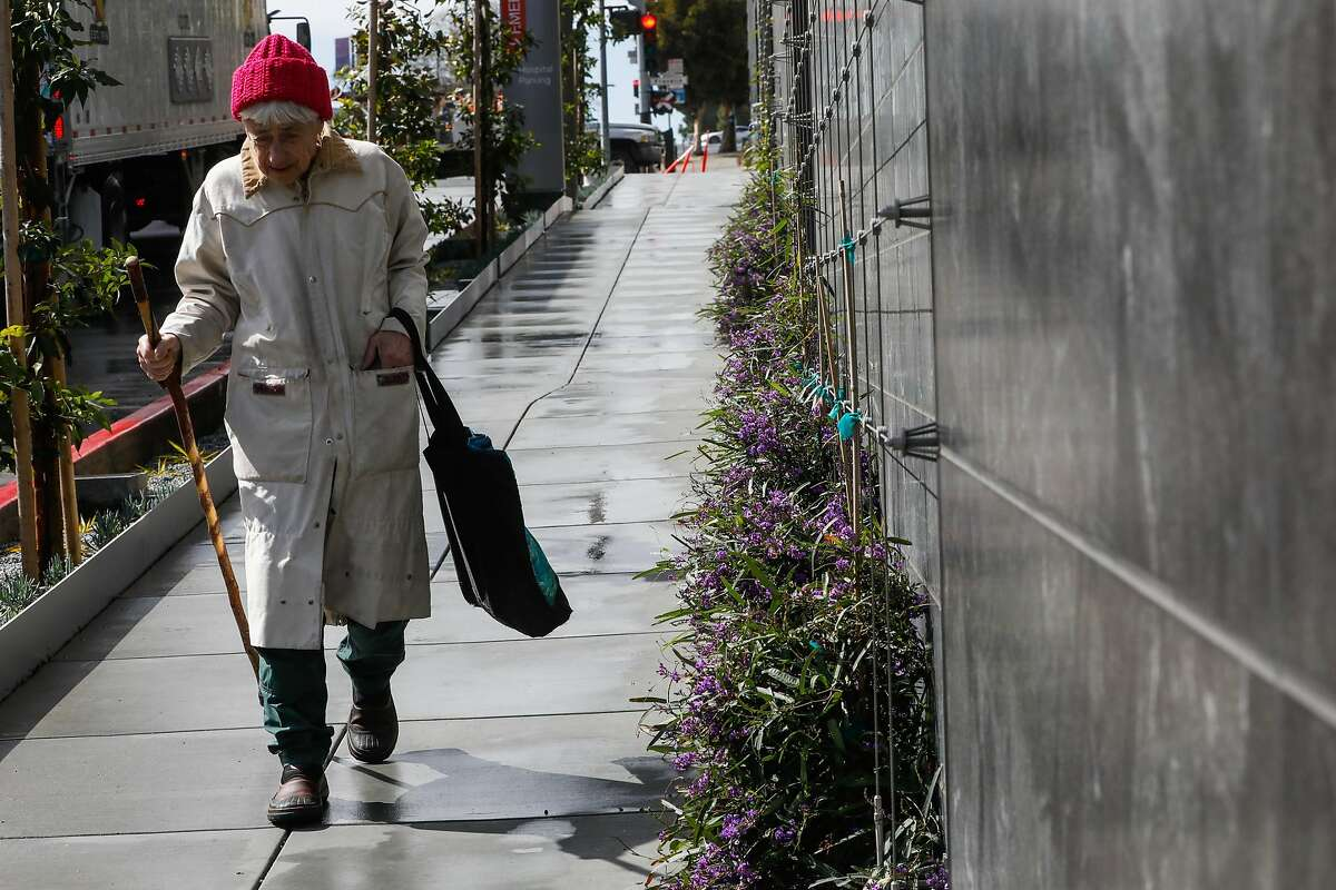 A woman passes by the landscaping outside of the California Pacific Medical Center on Van Ness Avenue in San Francisco, California, on Wednesday, March 6, 2019.