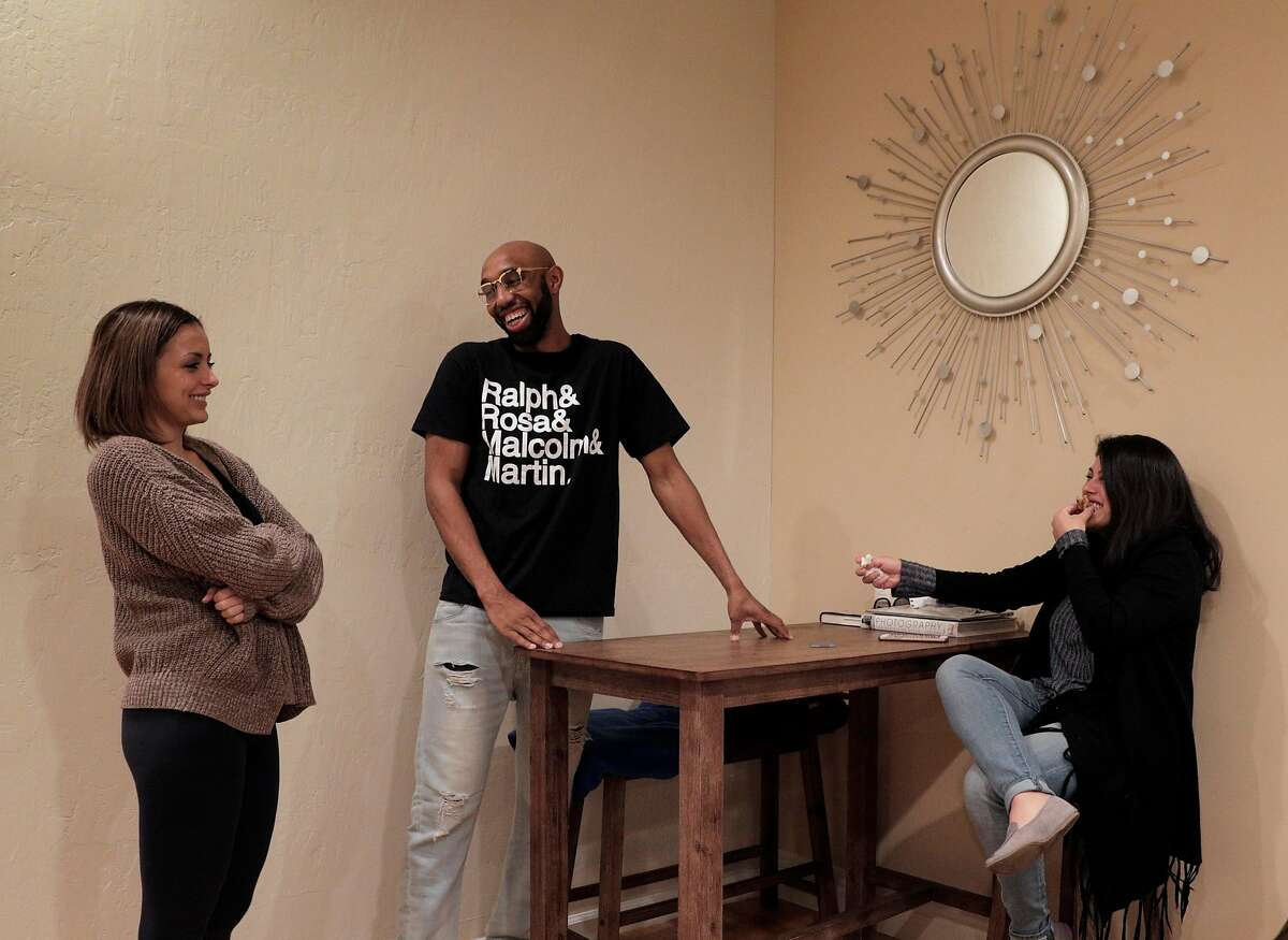 Housemates Jessica Bruno, left, Randy Jordan, center, and Carissa Villafa-a chat in the dining area of their Bungalow, co-living home in Oakland, Calif., on Monday, February 4, 2019. Bungalow is a co-living startup that leases big houses and then rents individual rooms that share a common spaces like kitchen, living room, and bathrooms.