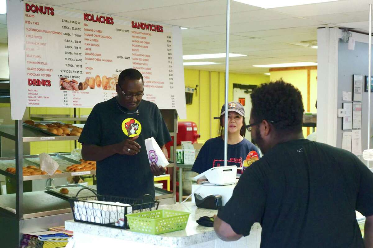 Noble McCoy and Tina Phoumlavanh assist Cody Walker at Donald's Donuts Wednesday, Aug. 23.
