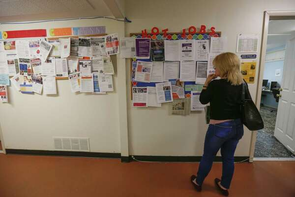A client looks at a bulletin board showing jobs in the Christian Community Service Center employment services program (CCSC) Thursday, Jan. 17, 2019, in Houston. CCSC is a coalition of churches working to reduce the effects of poverty in the local community.