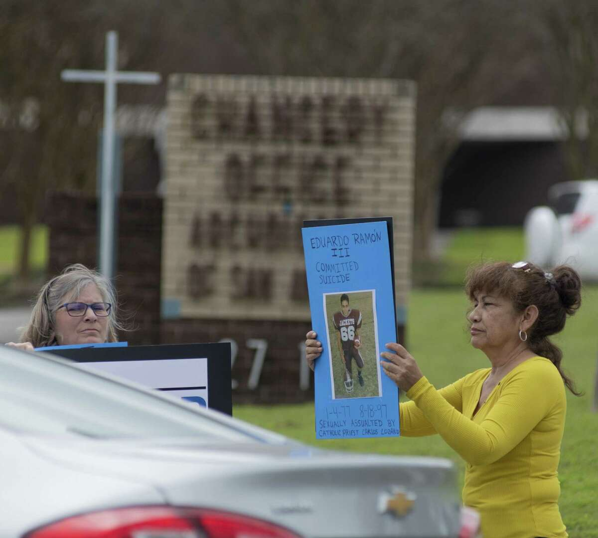 """Barbara Garcia Boeland, left, holds a sign with a picture of her son Eduardo Ramon III who committed suicided in 1997 after being sexually assaulted by Catholic priest Carlos Lozano and Patti Waller Koo holds a sing with another victim of sexual assault who did not want to be identified by name during press conference on Friday, March 8, 2019 outside the San Antonio archdiocesan headquarters discussing the finding of four more priests who have served in San Antonio and have been credibly accused abuser priests. These four priests were not named in the initial affidavit, according to members of the Survivors Network of those Abused by Priests. They urged church officials to add these and other names to their official ?""""accused?• list, warn several schools that a credibly accused abusive priest lives nearby, and disclose whether other alleged predators are living at the same facility."""