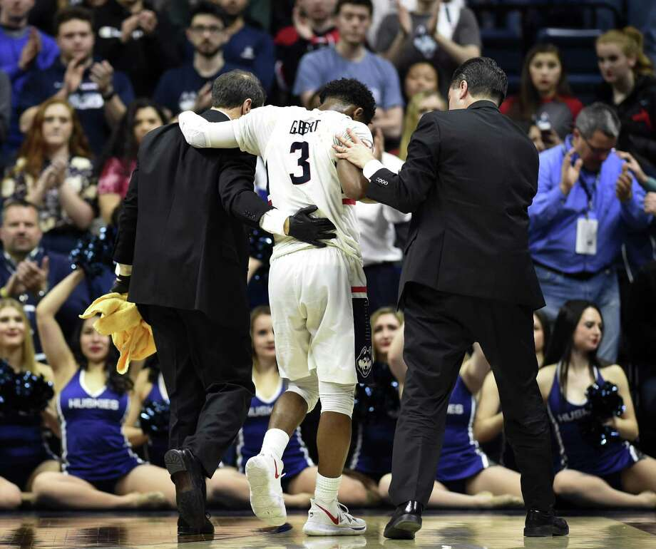 UConn's Alterique Gilbert (3) is helped off the court after suffering a facial laceration during the second half of Thursday's loss to Temple at Gampel Pavilion in Storrs. Gilbert's playing status for Sunday's regular season finale at East Carolina is uncertain. Photo: Stephen Dunn / Associated Press / Copyright 2019 The Associated Press. All rights reserved